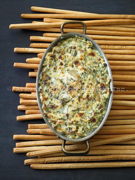 Large dish of baked artichoke dip, long crunchy breadsticks