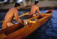 Traditional Hawaiian fishing canoe (made of acacia koa wood) being pulled ashore; Mauna Lani Resort, Hawaii