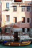 ITALY, Venice. View of a boat  parked in front of a home along a canal in the Castello district of Venice.