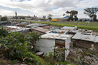 South Africa, Cape Town.  Guguletu Township Alongside Divided Highway to the Airport.  Note the satellite dish on one shack on the right.