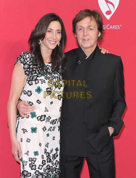 Nancy Shevell & Sir Paul McCartney .at The 2012 MusiCares Person of the Year Dinner honouring Paul McCartney at the Los Angeles Convention Center, West Hall in Los Angeles, California, USA, February 10th 2011..half length  white flowers green black jacket married couple husband wife arm around dress patterned                        .CAP/RKE/DVS.©DVS/RockinExposures/Capital Pictures.