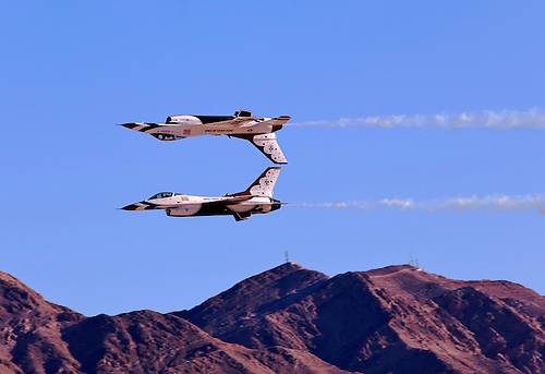 A thrilling moment as two Thunderbird fighter jets fly together one right-side up and the other up-side down at the Aviation Nation Openhouse airshow in Las Vegas, NV.