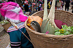A Hani woman carries on her back a basket full of purchases at a local market in Yuanyang, China. She carries a live duck and fresh greens, no doubt for dinner, and two hand-made brooms.