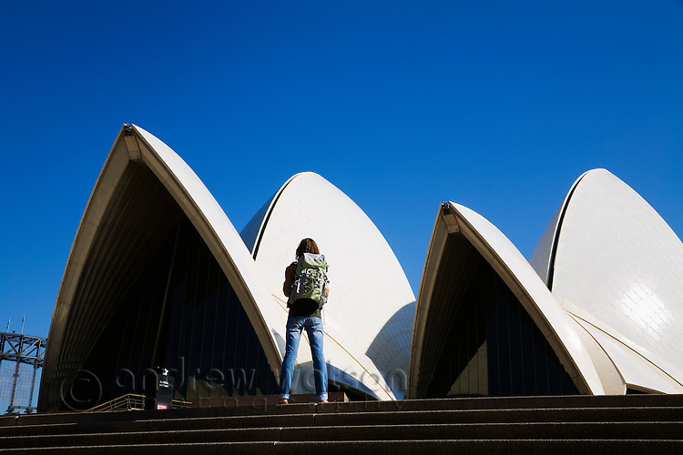 A backpacker stands atop the steps of the iconic Sydney Opera House.  Sydney, New South Wales, AUSTRALIA.
