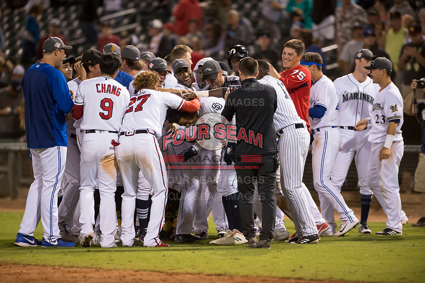 The AFL West team mobs left fielder Buddy Reed (85), of the Peoria Javelinas and San Diego Padres organization, after he scored the winning run in the Fall Stars game at Surprise Stadium on November 3, 2018 in Surprise, Arizona. The AFL West defeated the AFL East 7-6 . (Zachary Lucy/Four Seam Images)