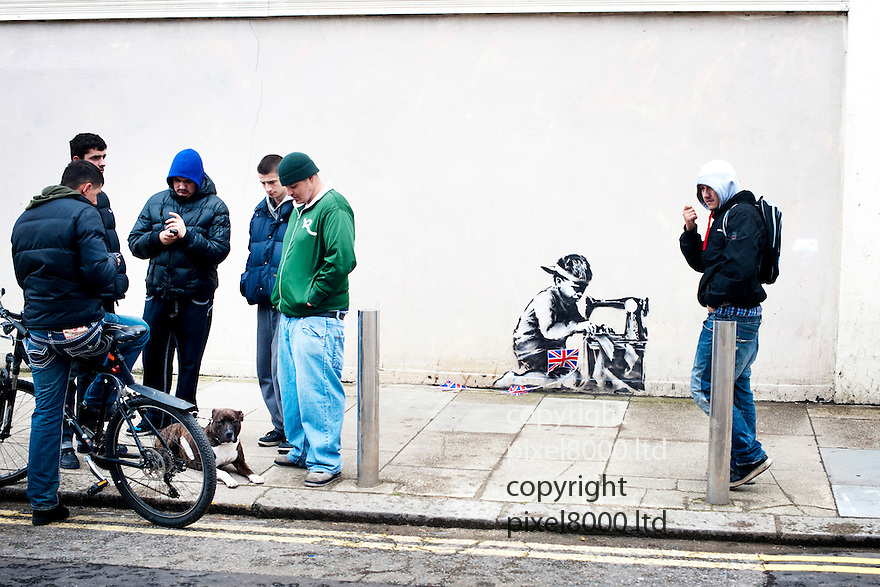 """Latest work believe to be by mysteriious graffiti artist Banksy ..It is  in Turnpike Lane London and painted on the wall of bargain store Poundland with an image depicting a child making Jubilee street party bunting in a sweatshop...The Banksy image depicts a young boy crouched over a sewing machine. The Jubilee-themed artwork has Union flag bunting similar to that sold in the store hung across the image...Some """"enterprising"""" local lads were asking for £5 from photographers to get a snap of the work. But once refused eventually gave up and moved out of the way.....Picture by Gavin Rodgers/ Pixel8000. 07917221968"""
