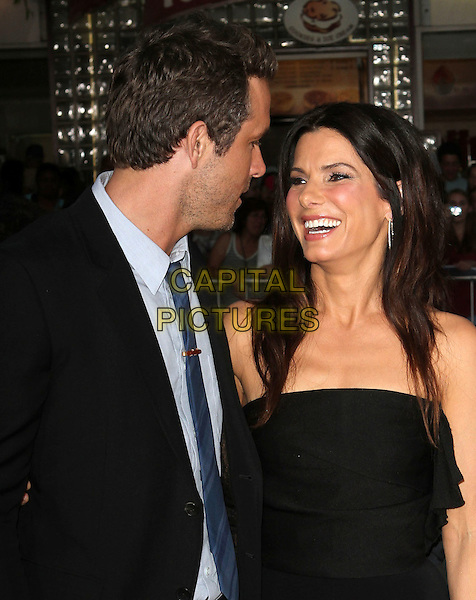 "Ryan Reynolds & Sandra Bullock.""The Change-Up"" Los Angeles Premiere Held At The Regency Village Theatre, Westwood, California, USA..August 1st, 2011.headshot portrait smiling black strapless blue tie stubble facial hair profile half length.CAP/ADM/KB.©Kevan Brooks/AdMedia/Capital Pictures."