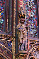 Detail of pillar made of three small columns on each side of a larger central column decorated with golden Castilian castles and flanked by a statue of apostle, nave of the upper chapel of La Sainte-Chapelle (The Holy Chapel), 1248, Paris, France. La Sainte-Chapelle was commissioned by King Louis IX to house his collection of Passion Relics, including the Crown of Thorns. The Sainte-Chapelle is considered among the highest achievements of the Rayonnant period of Gothic architecture. Picture by Manuel Cohen