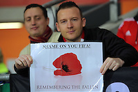 "A Wales fan with a ""Shame on you FIFA"" about the football governing body's decision not to alow home teams to wear the poppy during the 2018 FIFA World Cup Qualifier between Wales and Serbia at the Cardiff City Stadium, Wales, UK. Saturday 12 November 2016"