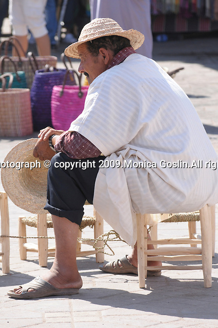 A man sits on a stool selling straw hats and stools in the busy marketplace of Marrakesh, Morocco.