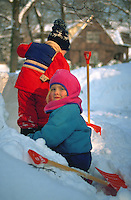 Two bundled up children playing in the snow.