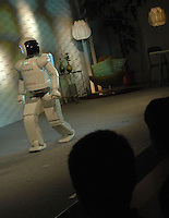An audience watch Honda's Asimo humanoid perform at Tokyo's National Museum of Nature and Science, Robot Exhibition. The Asimo which is designed to live with the family is able to fetch, clean and collect things.  According to Asimo's lead developer Masato Hirose the friendly home humanoid is no longer a distant dream.