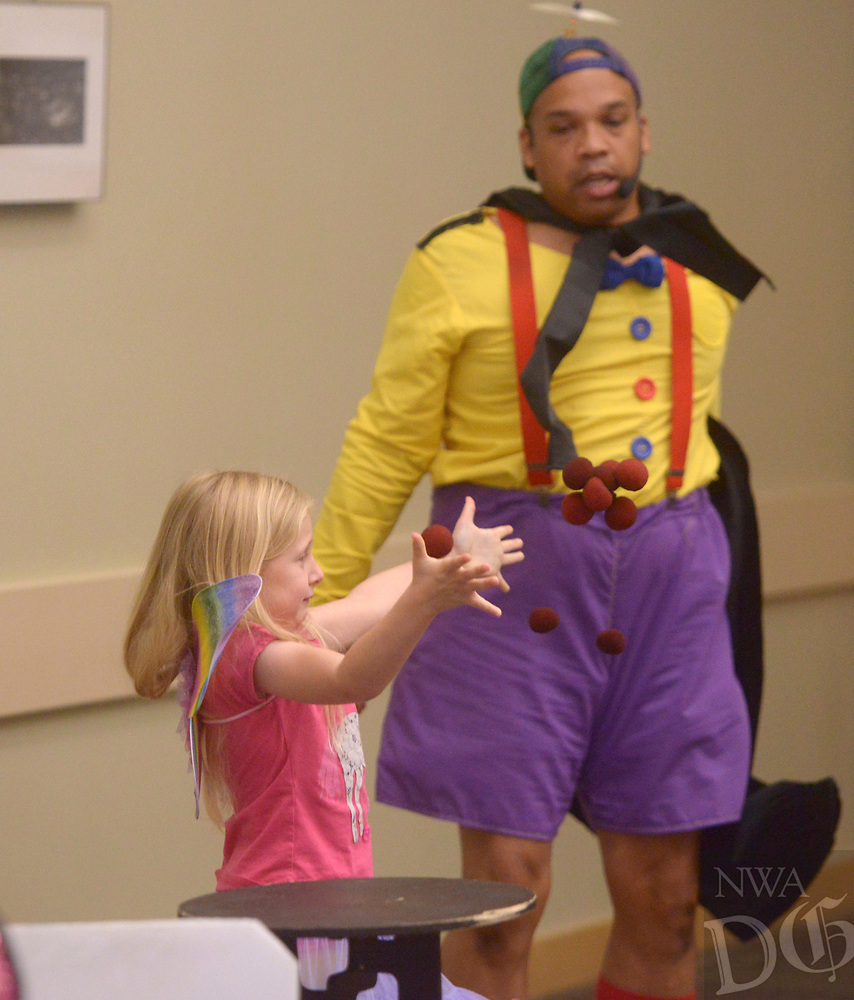 NWA Democrat-Gazette/BEN GOFF @NWABENGOFF<br /> Nora Grace Lowery, 5, of Bella Vista helps Tommy Terrific (Tommy Diaz of Little Rock) as an audience volunteer Thursday, July 6, 2017, during his Wacky Magic show for children at the Bentonville Public Library.