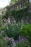Summer border at Haddon Hall next to stone wall with balustrade