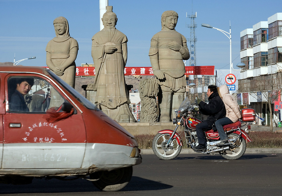 Traffic passes a junction with three sculptures featuring a Hui Muslim woman, a Han Chinese man, and a Roman soldier in Yongchang, a city near Liqian village. Some people  believe the area was originally settled by Roman soldiers about 2000 years ago, as the local inhabitants today have somewhat Caucasian features. This idea was first proposed by Homer Dubs, an Oxford University professor of Chinese history, who speculated in 1955 that some of the 10,000 Roman prisoners taken by the Parthians after the battle of Carrhae in southeastern Turkey in 53 B.C. made their way east to Uzbekistan to enlist with Zhi Zhi against the Han. Chinese accounts of the battle, in which Zhi Zhi was decapitated and his army defeated, note unusual military formations and the use of wooden fortifications foreign to the nomadic Huns. Dubs postulated that after the battle the Chinese employed the Roman mercenaries as border guards, settling them in Liqian, a short form of Alexandria used by the Chinese to denote Rome. ..