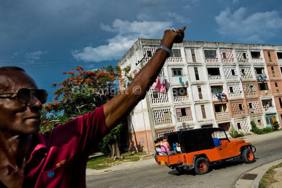 """A Cuban man waves to a friend from the apartment block in Abel Santamaría, a public housing suburb of Santiago de Cuba, Cuba, 31 July 2008. The Cuban economic transformation (after the revolution in 1959) has changed the housing status in Cuba from a consumer commodity into a social right. In 1970s, to overcome the serious housing shortage, the Cuban state took over the Soviet Union concept of social housing. Using prefabricated panel factories, donated to Cuba by Soviets, huge public housing complexes have risen in the outskirts of Cuban towns. Although these mass housing settlements provided habitation to many families, they often lack infrastructure, culture, shops, services and well-maintained public spaces. Many local residents have no feeling of belonging and inspite of living on a tropical island, they claim to be """"living in Siberia""""."""