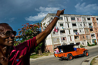 "A Cuban man waves to a friend from the apartment block in Abel Santamaría, a public housing suburb of Santiago de Cuba, Cuba, 31 July 2008. The Cuban economic transformation (after the revolution in 1959) has changed the housing status in Cuba from a consumer commodity into a social right. In 1970s, to overcome the serious housing shortage, the Cuban state took over the Soviet Union concept of social housing. Using prefabricated panel factories, donated to Cuba by Soviets, huge public housing complexes have risen in the outskirts of Cuban towns. Although these mass housing settlements provided habitation to many families, they often lack infrastructure, culture, shops, services and well-maintained public spaces. Many local residents have no feeling of belonging and inspite of living on a tropical island, they claim to be ""living in Siberia""."