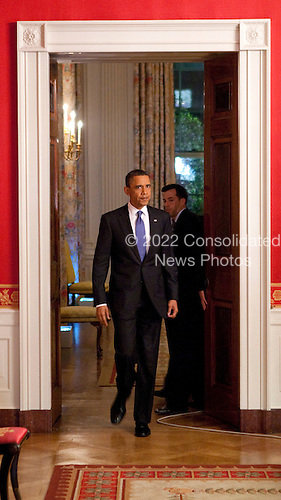 United States President Barack Obama walks through the Red Room to pose for photographers after reading a statement about a budget agreement to keep the U.S. government funded at the White House in Washington, D.C., U.S., on Friday, April 8, 2011. .Credit: Joshua Roberts / Pool via CNP