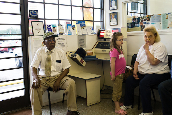 May 11, 2009. Rocky Mount, NC.. As unemployment has risen to 14% and the economy took a nosedive, Almand's Drug Store, an independently owned chain of 2 local stores, has seen a rise in uninsured customers having to choose between the drugs they have been prescribed and those they can afford putting the pharmacists in the position of health advisors and active participants in the health plans of their customers.. Brenda A. Kelly, right, and her granddaughter wait for their prescription to be filled.