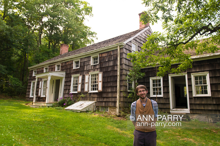 Old Bethpage, New York, USA. August 30, 2015. Matt, a seasonal staff member wearing traditional style American clothing, stands at the front of the Powell House at the end of a tour during the Old Time Music Weekend at Old Bethpage Village Restoration. The house was built in 1750 and is restored to its expanded 1855 size, and is the only building standing on its original location in the village.
