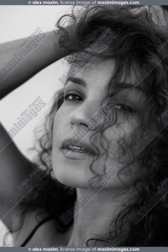 Close-up black and white beauty portrait of a young woman with sensual unguarded look and long curly dark hair falling on her beautiful face