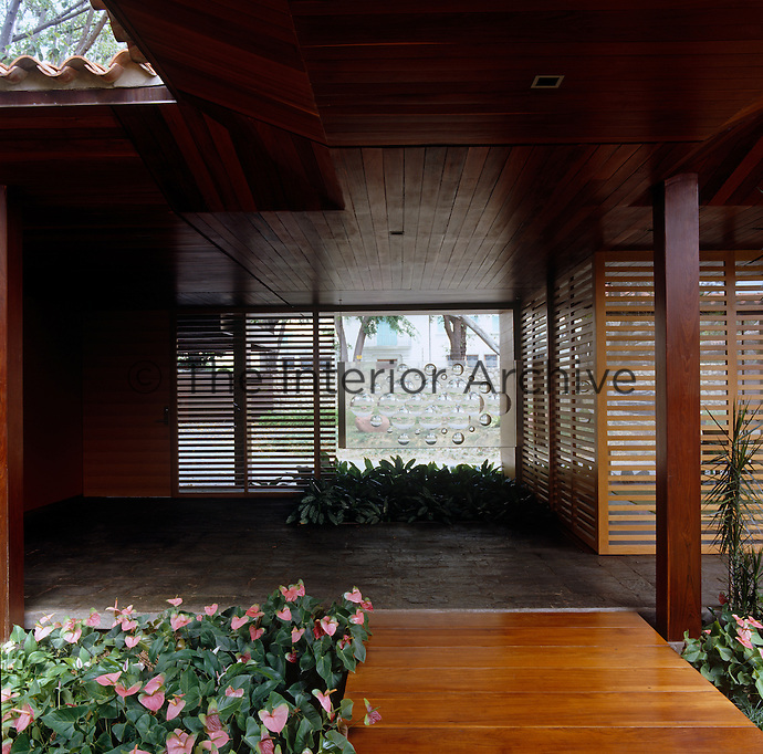 View along the decked and covered walkway that connects parts of this Japanese-style house with its modern entrance