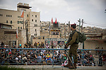 An Israeli soldier secures a parade marking the Jewish holiday of Purim, a celebration of the Jews' salvation from genocide in ancient Persia, as recounted in the Book of Esther, in the West Bank city of Hebron March 12, 2017.  Photo by: JINIPIX