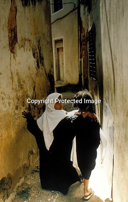 COTANZA35002.Country. Tanzania. Zanzibar. Two young  girls walking between buildings. 8/95 Traditional muslim dress..©Per-Anders Pettersson/iAfrika Photos