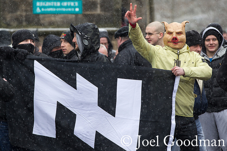 © Joel Goodman - 07973 332324 . 04/02/2012 . Rochdale , UK . A protester wearing a pig mask and carrying a flag bearing a Wolfsangel , a symbol used by the Nazi 2nd SS Panzer Division during the 2nd World War . The North West Infidels , a Nationalist group splintered from the EDL , protest outside Rochdale Town Hall . Protesters shout nationalist, Islamophobic and anti-Zionist slogans . Photo credit : Joel Goodman