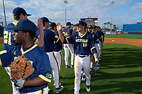 Michigan Wolverines Jake Bivens (18) high fives teammates after the second game of a doubleheader against the Canisius College Golden Griffins on February 20, 2016 at Tradition Field in St. Lucie, Florida.  Michigan defeated Canisius 3-0.  (Mike Janes/Four Seam Images)