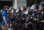 A protestor confronts a line of Seattle Police during the Solidarity Against Hate rally Sunday August 13, 2017 in Seattle.