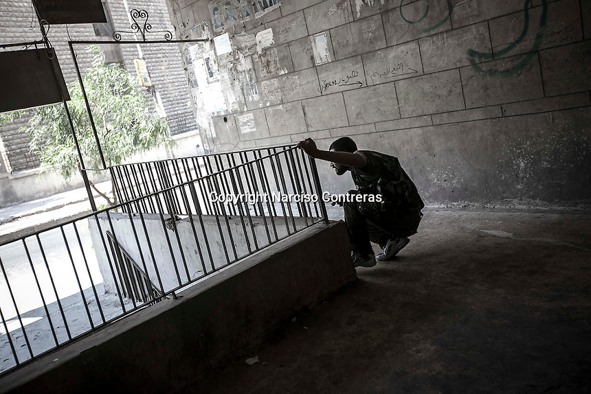 An opposition fighter sniper watches the position of a Syrian army sniper as he prepares to shoot him back at Bastan Basha residential neighborhood in the hub of Aleppo City.