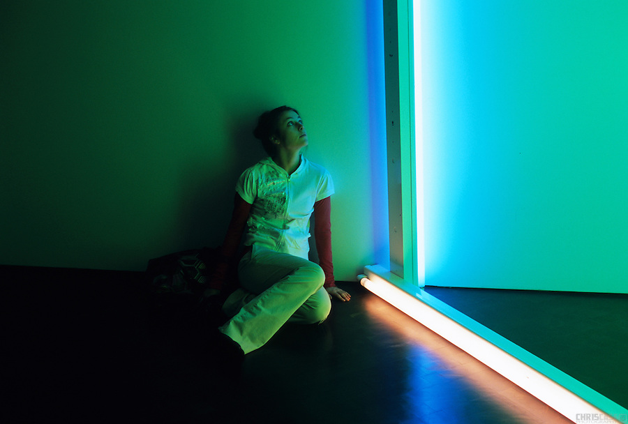 A visitor to the Denver Art Museum is lit by the glow of an art installation.