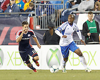 Montreal Impact midfielder Collen Warner (18) dribbles as New England Revolution midfielder Kelyn Rowe (11) closes. In a Major League Soccer (MLS) match, Montreal Impact (white/blue) defeated the New England Revolution (dark blue), 4-2, at Gillette Stadium on September 8, 2013.