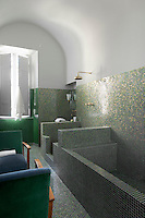 In the glamorous vaulted bathroom walls and floor are lined in green Bisazza mosaic with an unusual lilac-coloured grouting