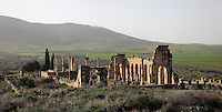 View of Volubilis, on a fertile plain in Northern Morocco, with the colonnaded facade which lined the Forum or marketplace and forms one side of the Roman Basilica, 217 AD, used as courts of justice and city governance, and the columns of the tetrastyle Capitoline Temple, rebuilt 218 AD on an existing shrine, in the distance. Volubilis was founded in the 3rd century BC by the Phoenicians and was a Roman settlement from the 1st century AD. Volubilis was a thriving Roman olive growing town until 280 AD and was settled until the 11th century. The buildings were largely destroyed by an earthquake in the 18th century and have since been excavated and partly restored. Volubilis was listed as a UNESCO World Heritage Site in 1997. Picture by Manuel Cohen