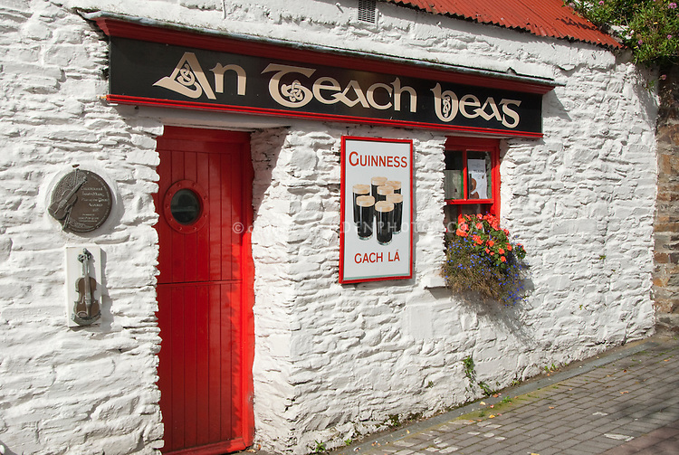 Whitewashed old Irish pub with red roof & Guinness beer sign, An Teach Beas (Gaelic for The Small House) in southwest Ireland