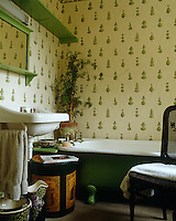 The bathroom is decorated with an Osborne & Little wallpaper and the bath tub, shelf and mirror frame have been picked out in green
