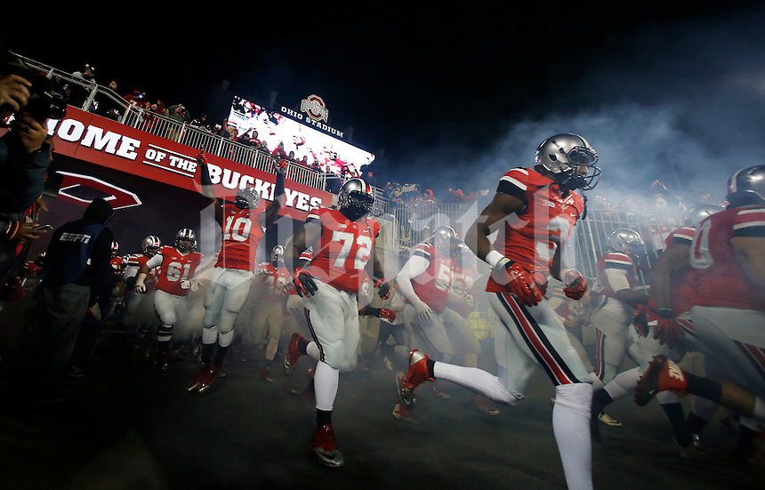 Ohio State players run out of the tunnel with smoke and pyrotechnics prior to the NCAA football game against the Illinois Fighting Illini at Ohio Stadium on Nov. 1, 2014. (Adam Cairns / The Columbus Dispatch)