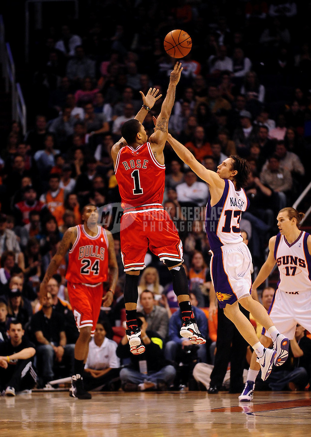 Jan. 22, 2010; Phoenix, AZ, USA; Chicago Bulls guard (1) Derrick Rose in shoots a three pointer above Phoenix Suns guard (13) Steve Nash in the first half at the US Airways Center. Mandatory Credit: Mark J. Rebilas-