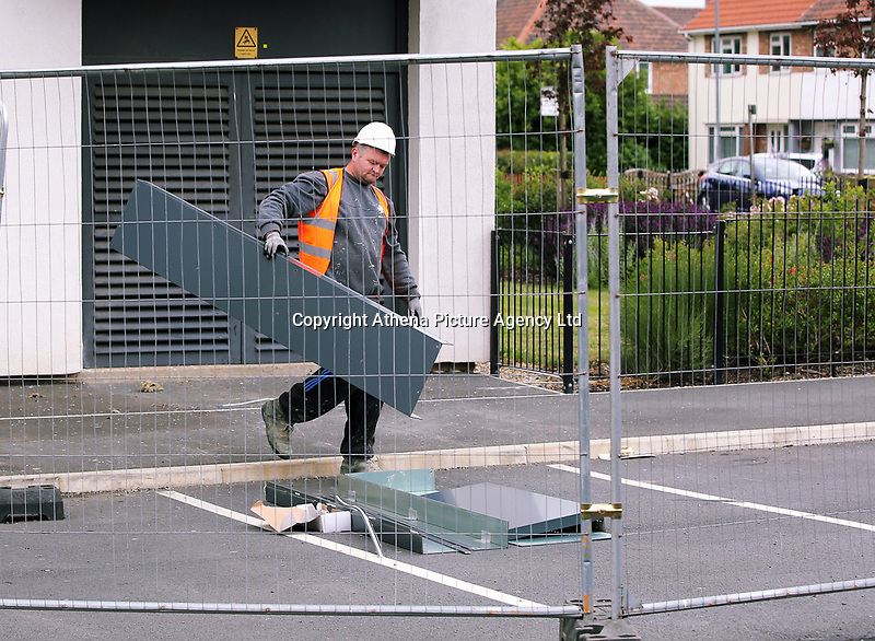 Pictured: A worker stacks cladding panels on the ground after being removed from Kennedy Gardens flats in Billingham. Tuesday 27 June 2017<br /> Re: Cladding is being removed by workers from the fascia of high-rise flats at Kennedy Gardens in Billingham, County Durham, England, UK