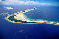 Aerial shot of cresent shaped Mili Atoll in the Marshall Islands, rimmed with white sand beaches set in a brilliant blue ocean with wispy clouds above.