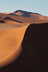 Tourist photographing sand dunes in Sossusvlei region of Namib-Naukluft National Park, Namibia.