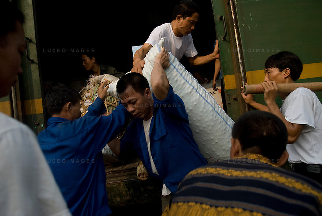 Workers unload supplies from a train heading from Hanoi to Sapa, Vietnam.