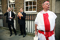 City workers and a man dressed in the flag of St. George watch members of the Parachute Regiment march by as the St. George's Day pagent arrives in Colman Street in the City of London.