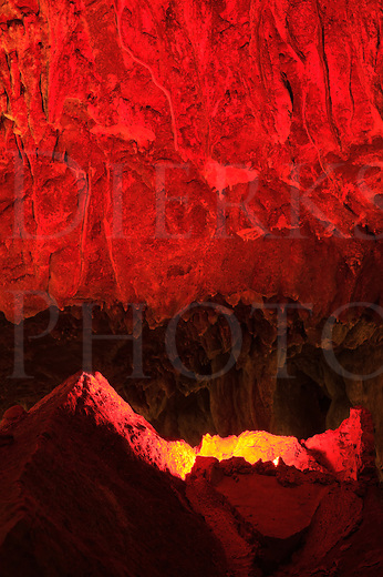 Cave ceiling rock illuminated by a red light, an ominous and eerie abstract image resembling hell or a volcano, shot underground.