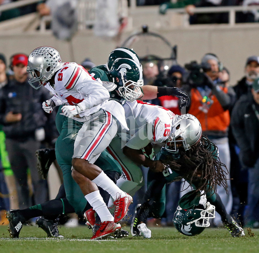 Ohio State Buckeyes quarterback J.T. Barrett (16) knocks the helmet off of Michigan State Spartans cornerback Trae Waynes (15) on a run during the 1st quarter at Spartan Stadium in East Lansing, Michigan on November 8, 2014.  (Dispatch photo by Kyle Robertson)