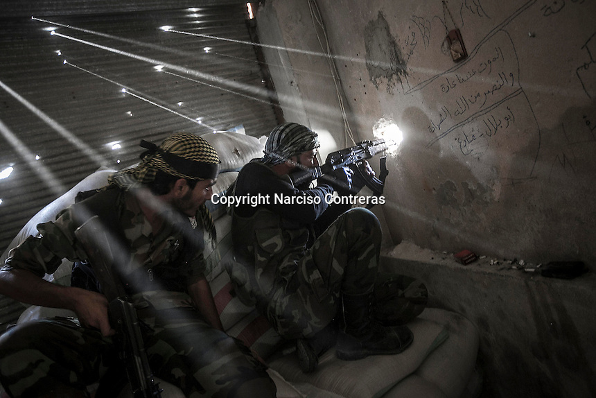 Rebel fighters belonging to the Javata Harria Sham Qatebee watch over the enemy position during skirmishes at the first line of fire in Karmal Jabl neighborhood, district of Arkup, at the northeast of Aleppo CIty.