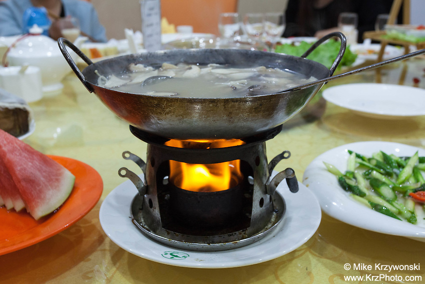 A mushroom soup dish kept warm by a fire canister after being served at a restaurant in Beijing, China
