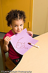 Education preschool 3 year olds girl holding up drawing of human figure vertical